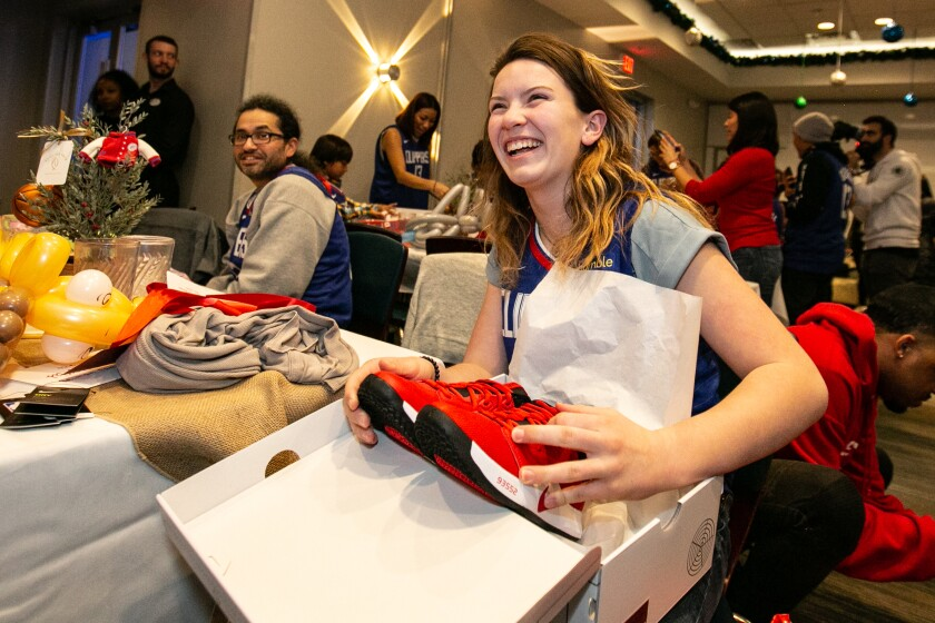 Rebecca Study, 13, opens a gift of new sneakers from LA Clippers star Paul George.