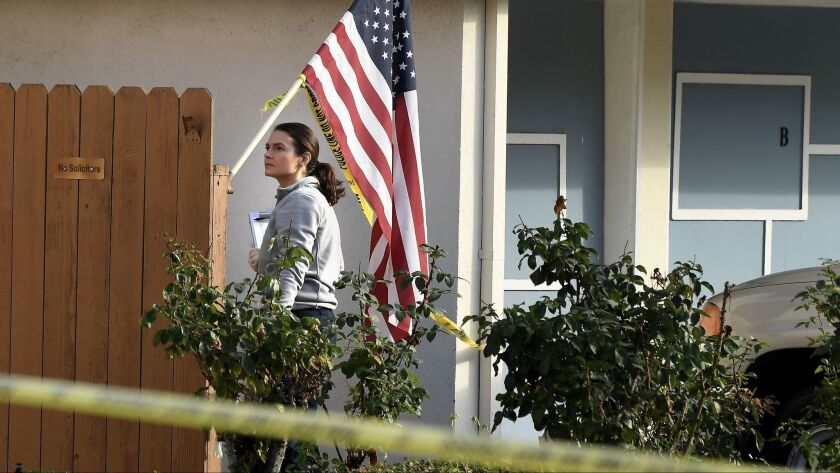 An investigator searches for evidence at the home of a retired L.A. County sheriff's deputy who was shot Thursday morning while answering his door.