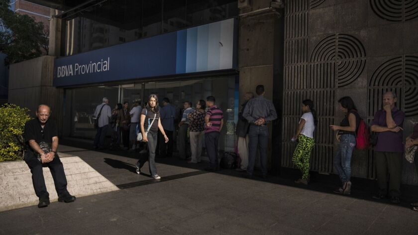 People line up to withdraw cash at an ATM in Caracas.