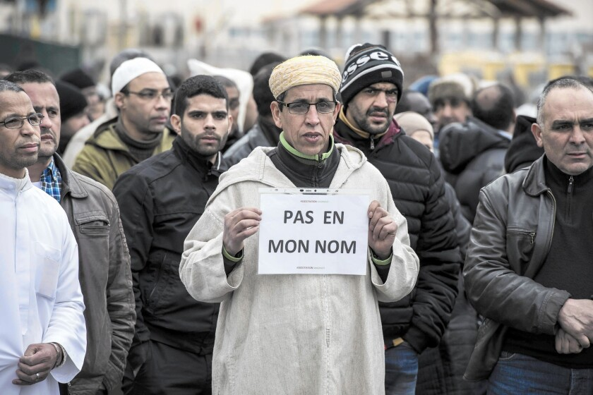 "A Muslim man at a gathering near a mosque in Saint-Etienne, France, holds a sign reading ""Not in my name"" after the deadly attack on the satirical magazine Charlie Hebdo."
