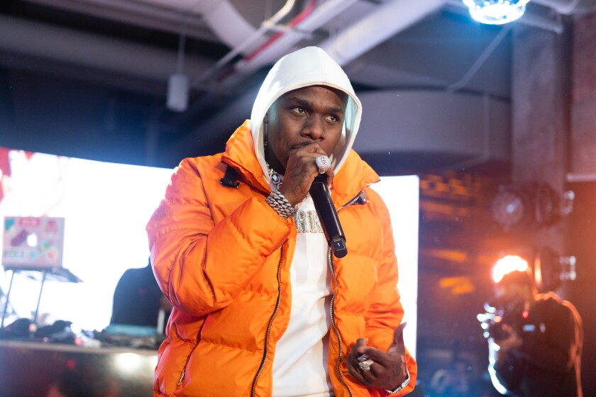 A man in an orange coat and white hoodie holding a microphone