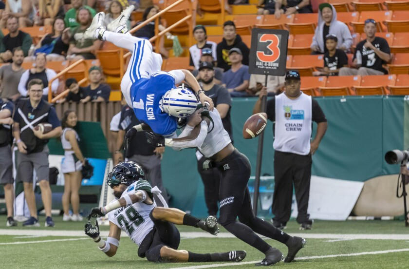 BYU quarterback Zack Wilson fumbles the ball after he's hit by Hawaii defensive backs Donovan Dalton (29) and Eugene Ford during the Hawaii Bowl on Dec. 24, 2019, in Honolulu.