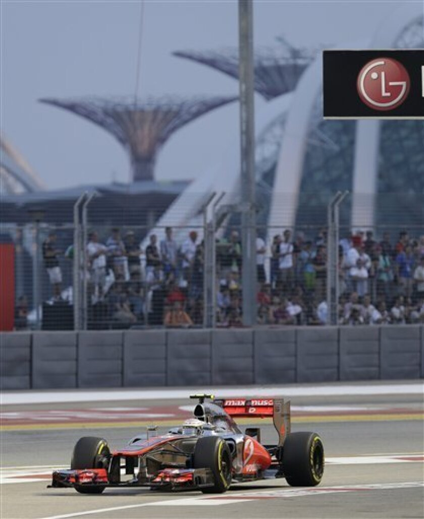 McLaren Formula One driver Lewis Hamilton of Britain drives into pit lane during the third practice session for the Singapore Formula One Grand Prix on the Marina Bay City Circuit in Singapore, Saturday, Sept. 22, 2012. (AP Photo/Mark Baker)