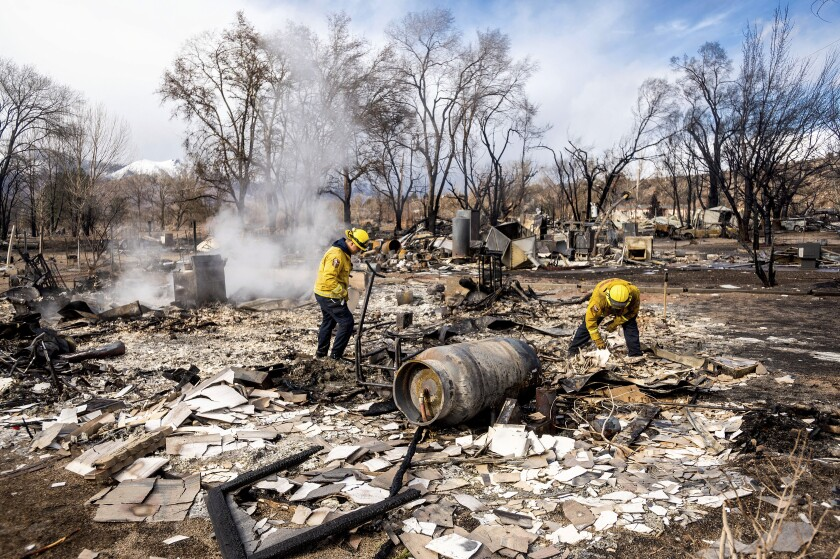 Firefighters sift through debris after the Mountain View fire tore through the town of Walker in Mono County.