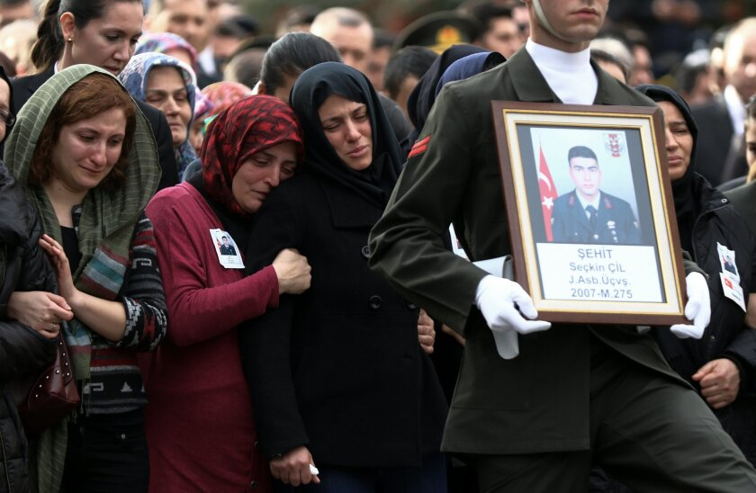 Family members attend funeral prayers for Turkish army officer Seckin Cil, who was killed in Sur, Diyarbakir Wednesday, in Ankara, Turkey, Thursday, Feb. 18, 2016. Six soldiers were killed after PKK rebels detonated a bomb on the road linking the cities of Diyarbakir and Bingol in southeastern Turk