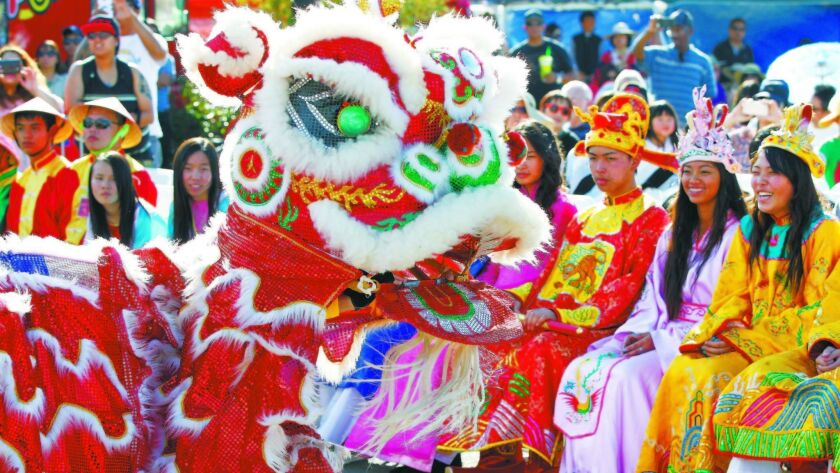 Teens in costume watch the lion dance.