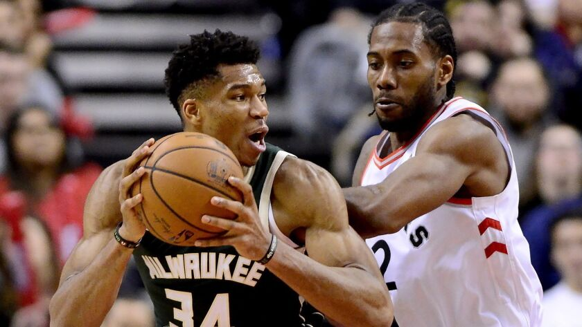 Raptors forward Kawhi Leonard (2) puts pressure on Bucks forward Giannis Antetokounmpo (34) during the second half Sunday.