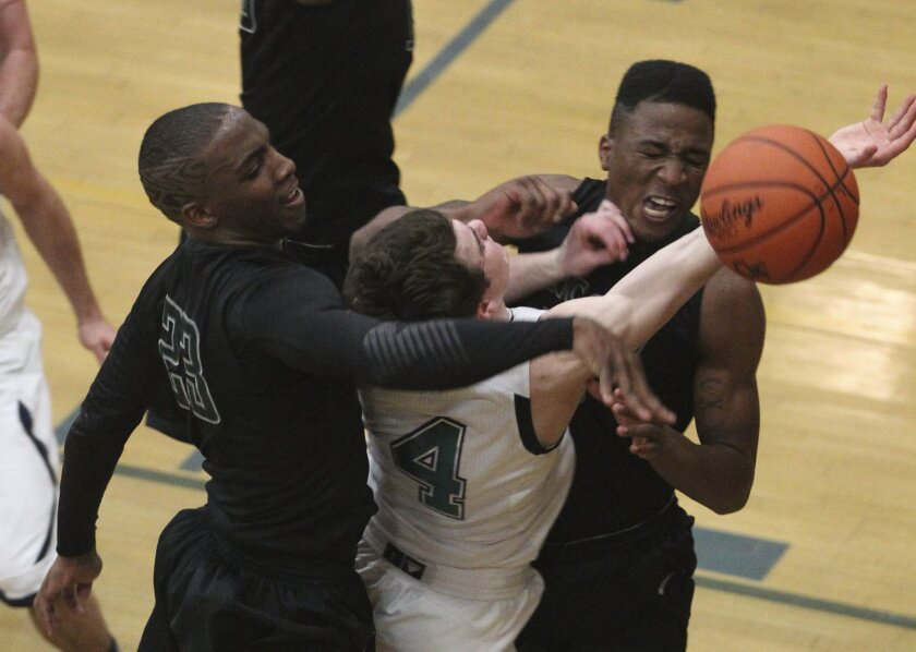 CIF playoff basketball between Lincoln High School and LA Costa Canyon High School at La Costa Canyon. La Costa Canyon #4 Tommy McCarthy drives to the basket and is fouled by Lincoln as #23 Tyree Robinson and #10 Kevon Mitchell  go up to block him in the second half..