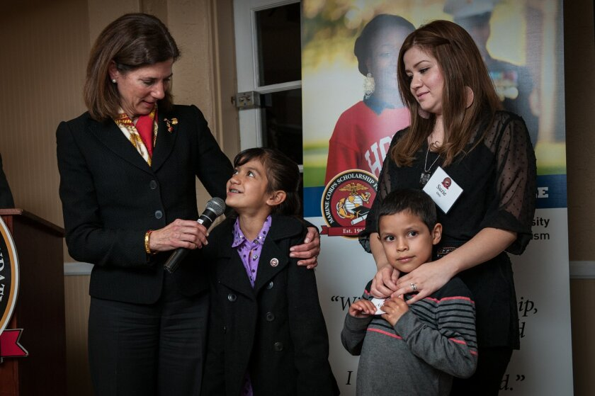 Marine Corps Scholarship Foundation's president and CEO, Margaret B. Davis gives the microphone to scholarship recipient Isabel Ortiz while her mother Susie Ortiz and brother Andrew look on.