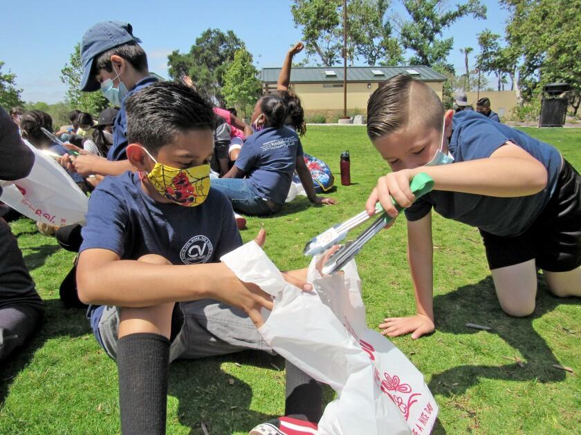 Johnson Elementary School students Arturo Garcia Jr. (left) and Kekona Alameda clean up at Mast Park in Santee on Tuesday