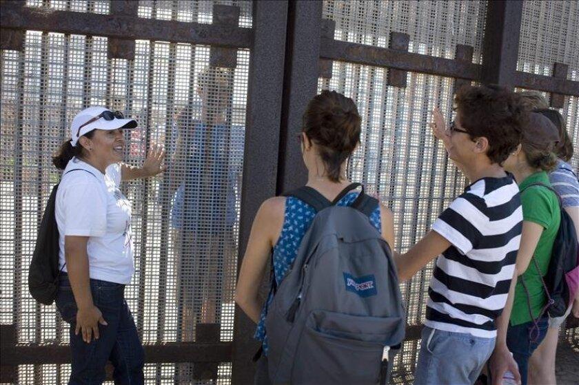 """Adriana Jasso, del """"American Friends Service Committee"""", habla con un grupo de estudiantes de la universidad de Pomona, que visitan la frontera entre Estados Unidos y México. Unas dos mil personas han acudido en lo que va del año al Parque de la Amistad de San Diego los fines de semana para ver a sus familiares y amigos que viven en México. EFE"""