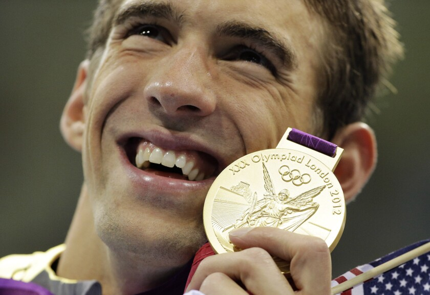 FILE - In this July 31, 2012 file photo, United States' Michael Phelps poses with his gold medal for the men's 4x200-meter freestyle relay swimming final at the Aquatics Centre in the Olympic Park during the 2012 Summer Olympics in London. (AP Photo/Matt Slocum, File)