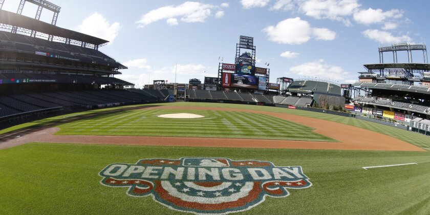 The logo to mark opening day is displayed along the first base line as workers prepare Coors Field on Thursday, April 9, 2015, in Denver. The Rockies are scheduled to face the Chicago Cubs in the team's home opener. (AP Photo/David Zalubowski)