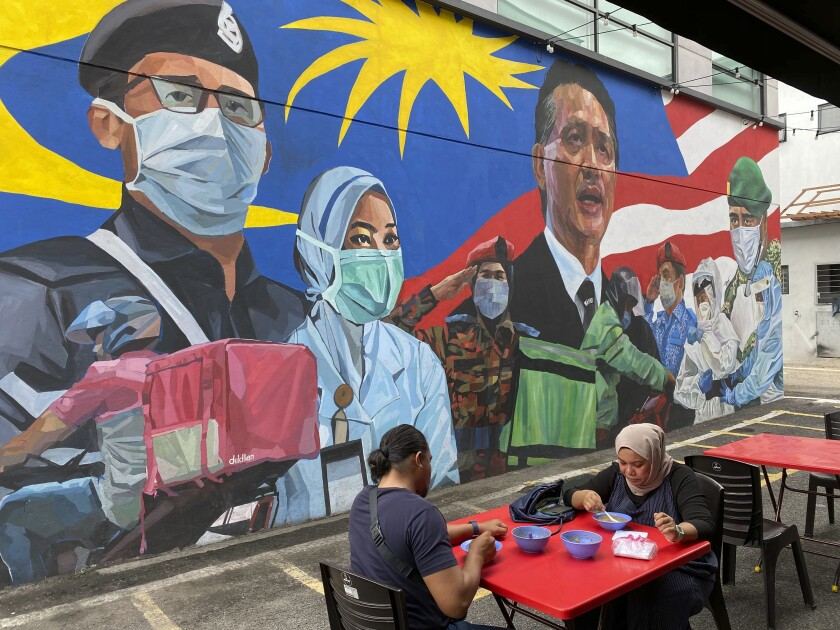 A Malay couple have lunch next to a graffiti tribute to Malaysian workers on the frontlines against the COVID-19 coronavirus at Damansara in Selangor, outside Kuala Lumpur, Malaysia, Saturday, Nov. 7, 2020. Malaysia extended restricted movements in its biggest city Kuala Lumpur, neighboring Selangor state and the administrative capital of Putrajaya from Wednesday in an attempt to curb a sharp rise in coronavirus cases. (AP Photo/Vincent Thian)