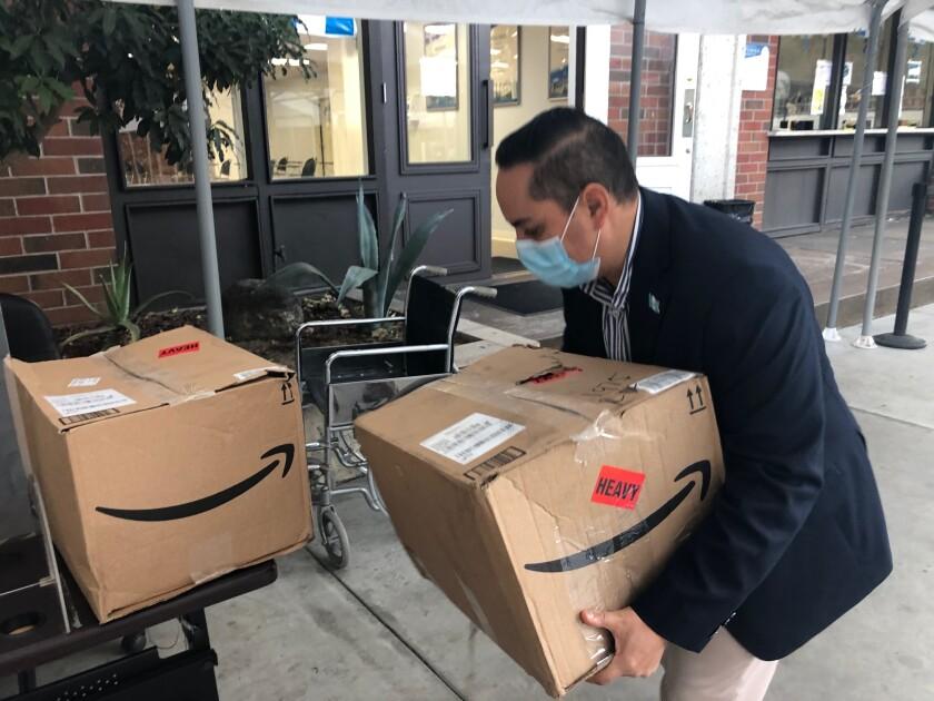 El cónsul guatemalteco en Los Ángeles, Tekandi Paniagua, carga una caja con desinfectantes.