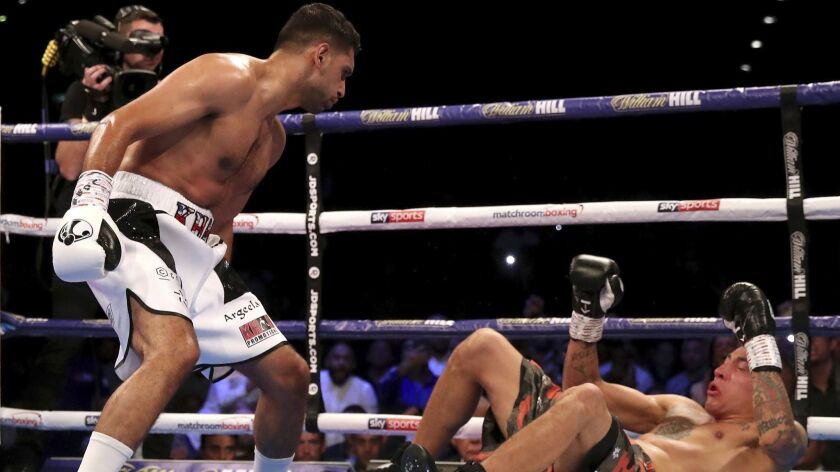 Amir Khan, left, knocks down Samuel Vargas in action during their Welterweight contest at Arena Birmingham, in Birmingham, England, Saturday Sept. 8, 2018. (Nick Potts/PA via AP)