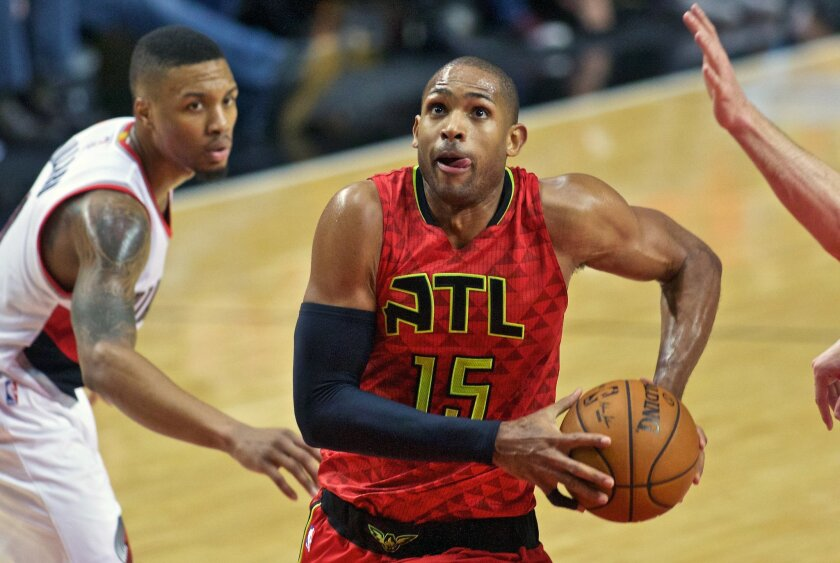 FILE - In this Jan. 20, 2016, file photo, Atlanta Hawks center Al Horford drives past Portland Trail Blazers guard Damian Lillard during the second half of an NBA basketball game in Portland, Ore.  The Hawks All-Star said Wednesday, Feb. 17, 2016,  he expects to remain in Atlanta, and he is the ide