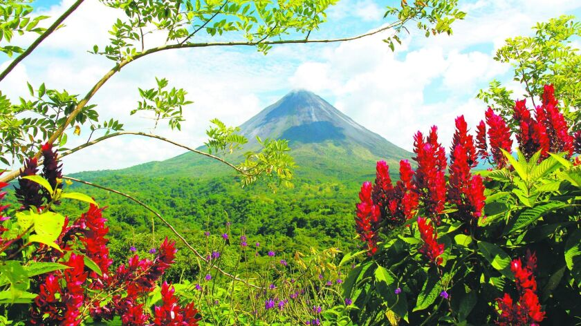 The photogenic, nearly 5,500-foot-tall Arenal volcano graces the sky in Costa Rica with its perfect conical shape.