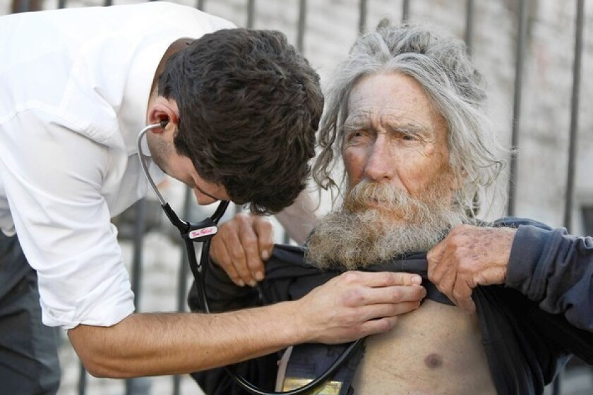"""Tom Fadial, a third-year UCLA medical student, listens to the heart of patient Stanley Rudolph, 75, a homeless Korean War-era veteran, who took advantage of services offered by the Mobile Clinic Project. """"I'm what they call off the grid,"""" Rudolph said."""