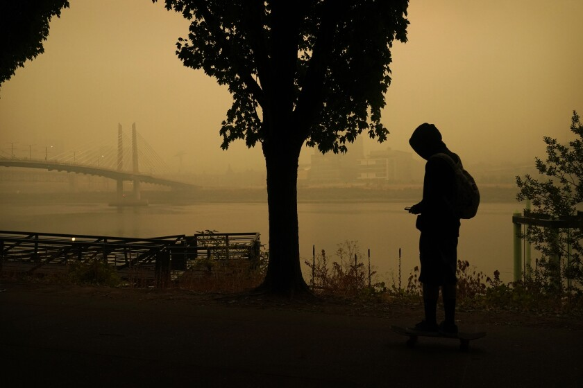 A person rides a skateboard along the Willamette River as smoke from wildfires partially obscures the Tilikum Crossing Bridge, Saturday, Sept. 12, 2020, in Portland, Ore. (AP Photo/John Locher)