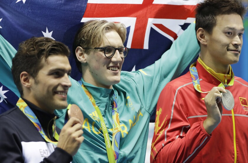 Winner Australia's Mack Horton, center, second placed Italy's Gabriele Detti, left, and third placed China's Sun Yang hold their medals after the men's 400-meter freestyle in Rio de Janeiro.