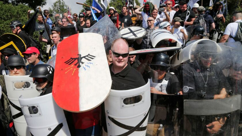 FILE - In this Aug. 12, 2017 file photo, white nationalist demonstrators use shields as they guard t
