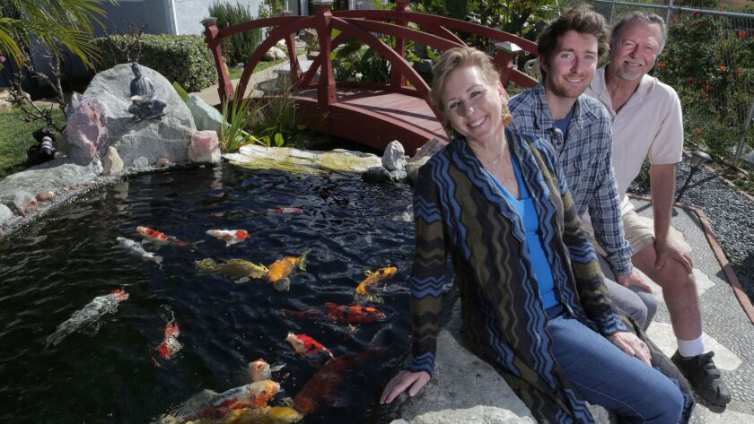 Kelly Van Jen with her son Jason, 22, and husband James beside a koi pond at their company called Ko