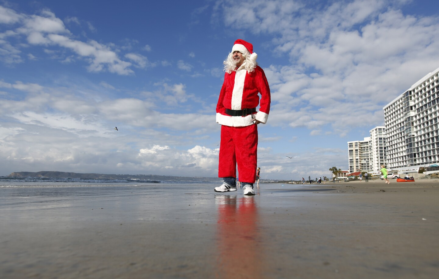 Alan Zada, dressed as Santa Claus, came down to greet surfers during the 9th Annual URT Santa Surf Off and Toy Drive in Coronado on Dec. 24, 2019.