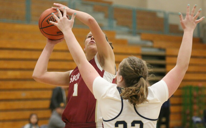 Mission Hills' Amber Schmidt powers to the hoop against LCC's Haley Dumiak.