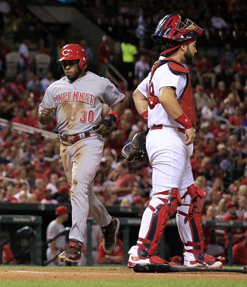 Cincinnati Reds' Jason Bourgeois, left, scores past St. Louis Cardinals catcher Tony Cruz, right, on a single by Brandon Phillips during the first inning of a baseball game against the St. Louis Cardinals on Monday, Sept. 21, 2015, in St. Louis. (AP Photo/Jeff Roberson)