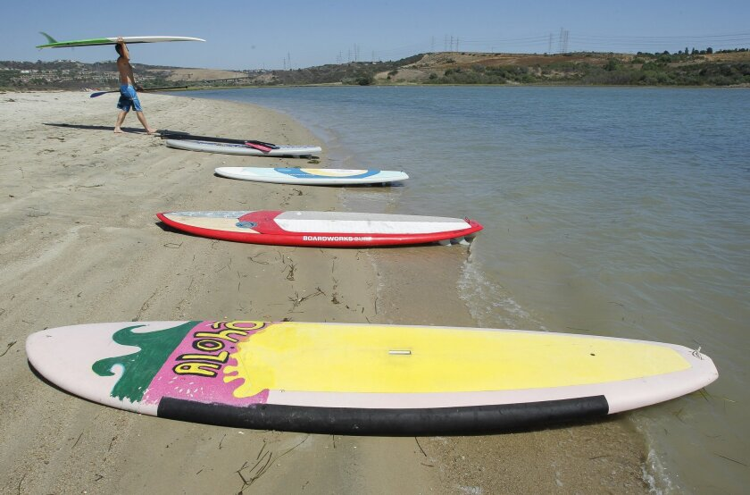 Standup paddle boards lie on the beach as Garth Davis carries his up to the shore Ben S as they spent the day on the beach at the Agua Hedionda Lagoon, near Bayshore Drive, in Carlsbad on Wednesday.