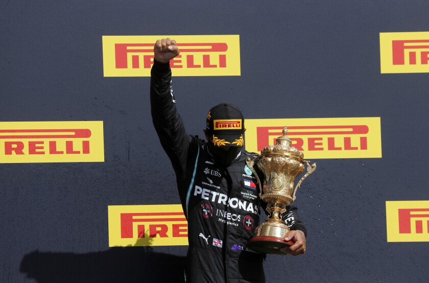 Lewis Hamilton holds his trophy on the podium after the British Formula One Grand Prix in Silverstone, England.