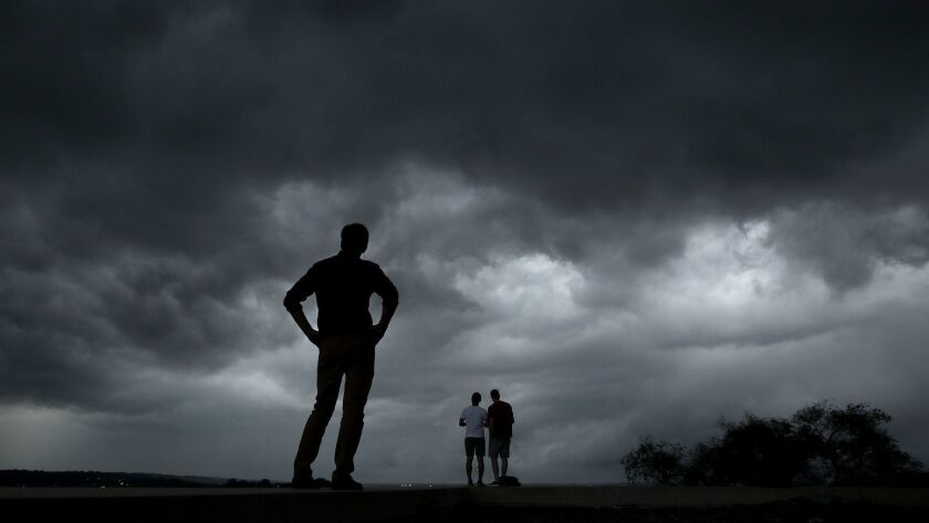People in downtown Kansas City, Mo., watch a storm approach.