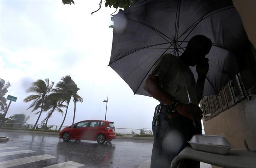 Un hombre camina bajo la lluviaocasionada por el paso del huracán María en San Juan (Puerto Rico). EFE/Archivo