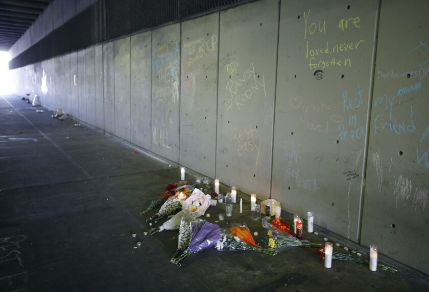 Candles burn at a memorial at the crash site that killed at three people on B Street near San Diego City College on Tuesday
