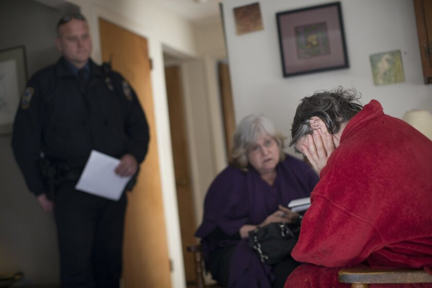 In this Wednesday, Jan. 6, 2016, photo, Colerain Township Police Det. Dave Hubbard, left, and Nan Franks, CEO of Greater Cincinnati Addiction Services Council, center, meet with a heroin user, who requested to remain anonymous, five days after she nearly died from a heroin overdose in Colerain Town