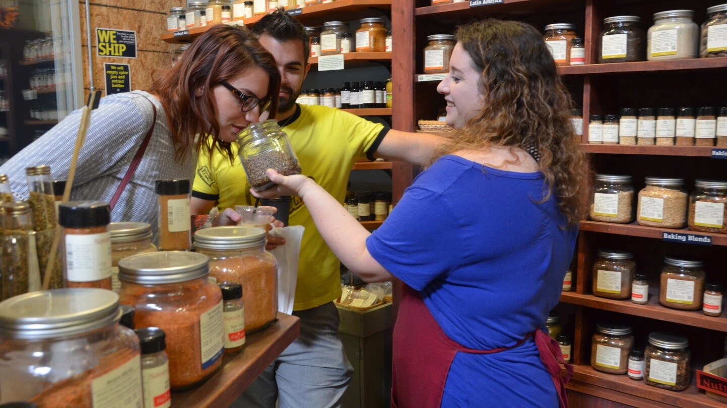 Delphia McCarty takes a whiff of a jar of Pike Place Protein Rub offered by Clarice Hemenway at Savory Spice Shop on Small Business Saturday at SOCO and the OC Mix in Costa Mesa.