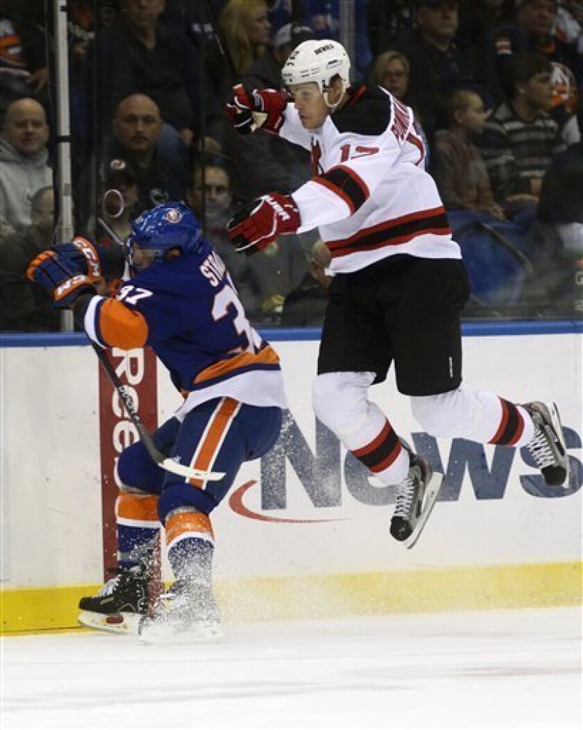 New Jersey Devils' Alexei Ponikarovsky, right, jumps out of the way of New York Islanders' Brian Strait in the first period of an NHL hockey game in Uniondale, N.Y., Saturday, Feb. 16, 2013. (AP Photo/Henny Ray Abrams)