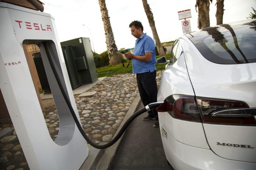 Gunjan Bagla of Cerritos charges his Tesla at a supercharger station near Coalinga, Calif., last year.