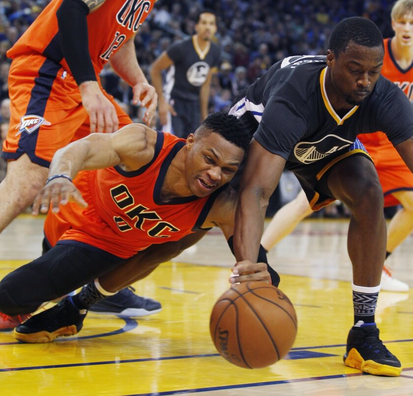 Oklahoma City Thunder's Russell Westbrook, left, and Golden State Warriors' Harrison Barnes struggle for a loose ball during the first half of an NBA basketball game Saturday, Feb. 6, 2016, in Oakland, Calif. (AP Photo/George Nikitin)