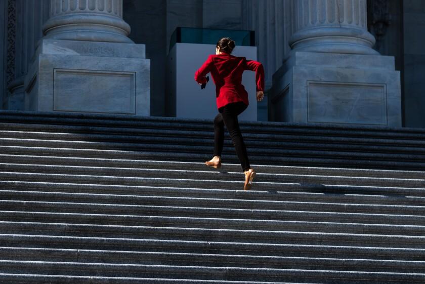 La representante Alexandria Ocasio-Cortez sube corriendo los escalones del Capitolio con una chaqueta roja y tacones cortos.