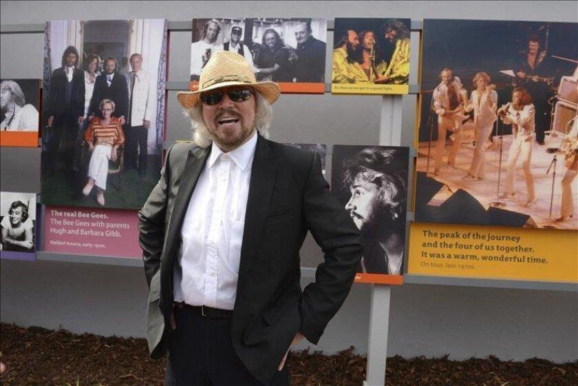 El músico australiano Barry Gibb posa junto a varias fotografías de Barry, Robin y Maurice Gibbs, componentes del grupo musical Bee Gees, durante la inauguración oficial del Paseo de lo Bee Gees en Redcliffe, norte de Brisbane (Australia). EFE/Archivo
