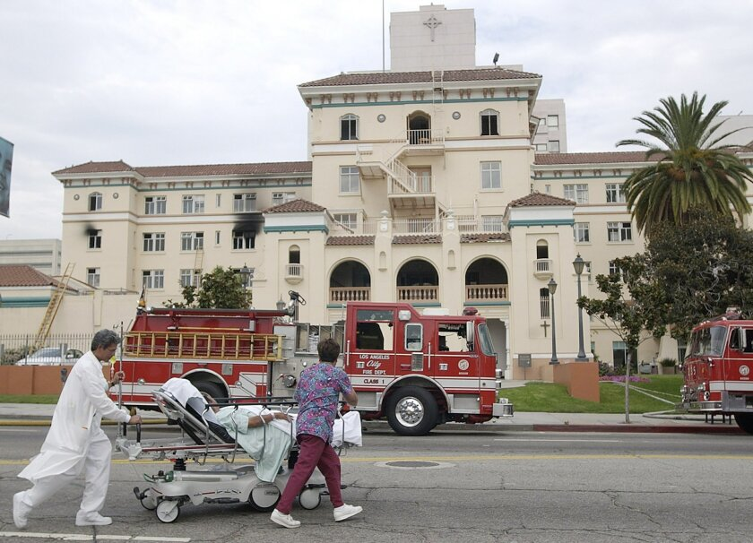 FILE - In this July 22, 2003, file photo, nurses evacuate a patient after a fire broke out on the third floor of the 434-bed the formerly named Queen of Angels-Hollywood Presbyterian Medical Center, with visibly blackened windows, in the Hollywood section of Los Angeles. The FBI says Wednesday, Feb
