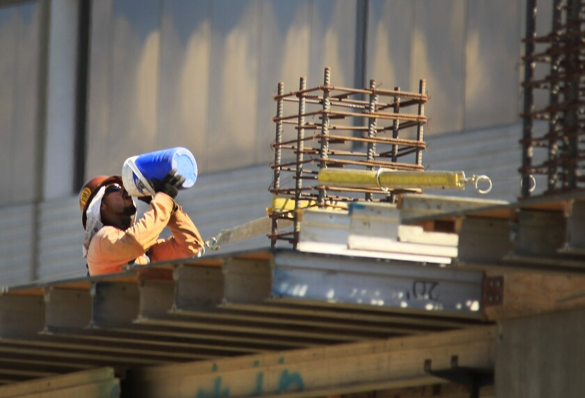 A construction worker takes a drink during a heat wave