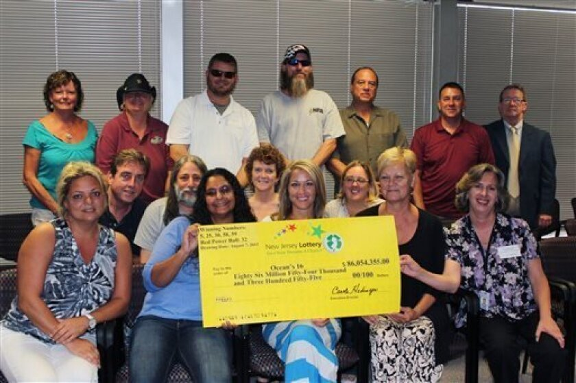 In this Monday, Aug. 12, 2013 photo provided by the New Jersey Lottery, the 16 unidentified workers from an Ocean County garage in a New Jersey shore community hit hard by Superstorm Sandy pose with a winner's check from the $448 million Powerball drawing, on Wednesday, Aug. 7. The group had one of three winning tickets in the lottery. (AP Photo/New Jersey Lottery, Sam Fromkin)