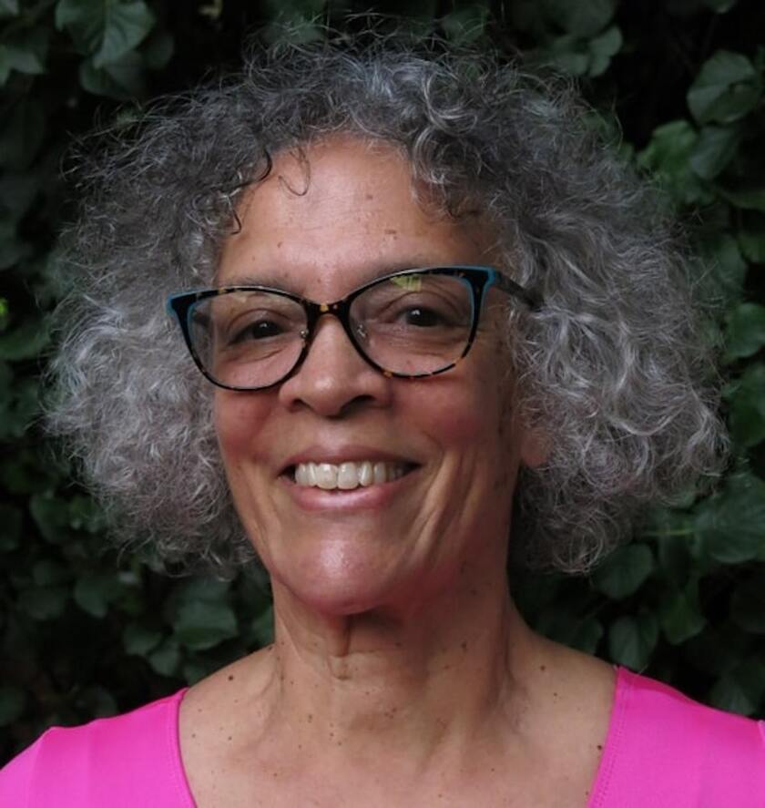 A women with gray hair, glasses and a bright pink top smiles
