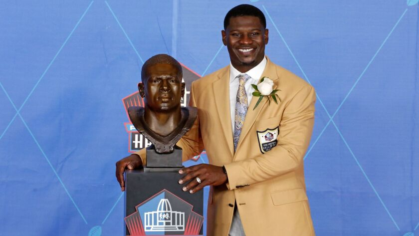 LaDainian Tomlinson poses with a bust of himself during induction ceremony at Pro Football Hall of Fame in 2017.
