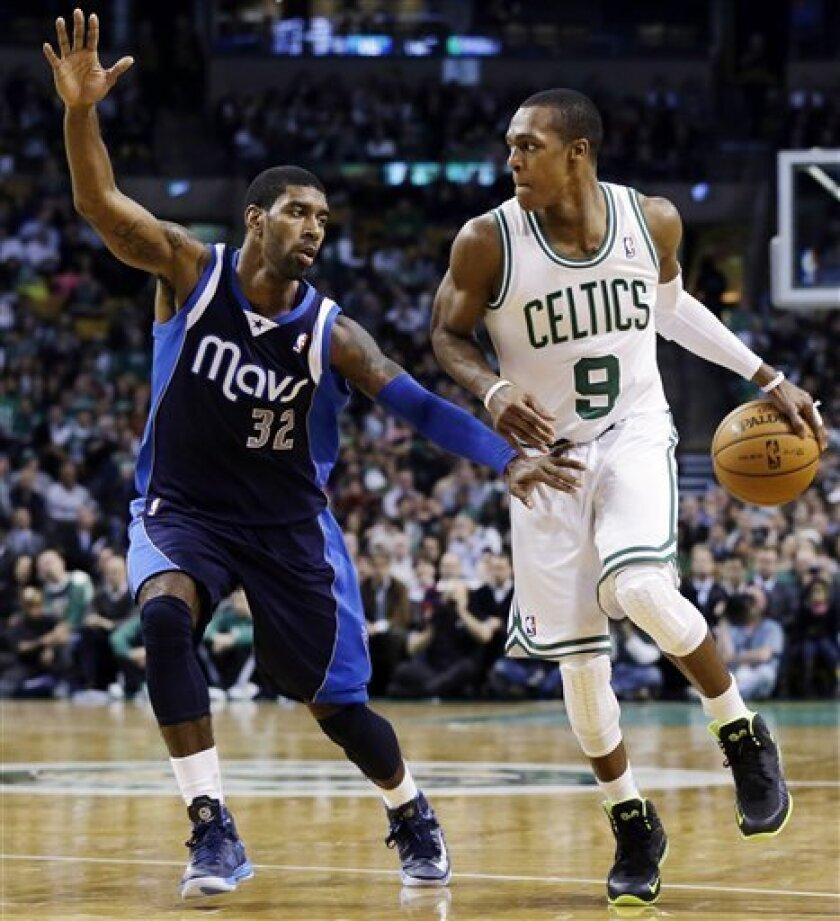 Boston Celtics guard Rajon Rondo (9) handles the ball against Dallas Mavericks shooting guard O.J. Mayo (32) during the second quarter of an NBA basketball game in Boston, Wednesday, Dec. 12, 2012. (AP Photo/Elise Amendola)