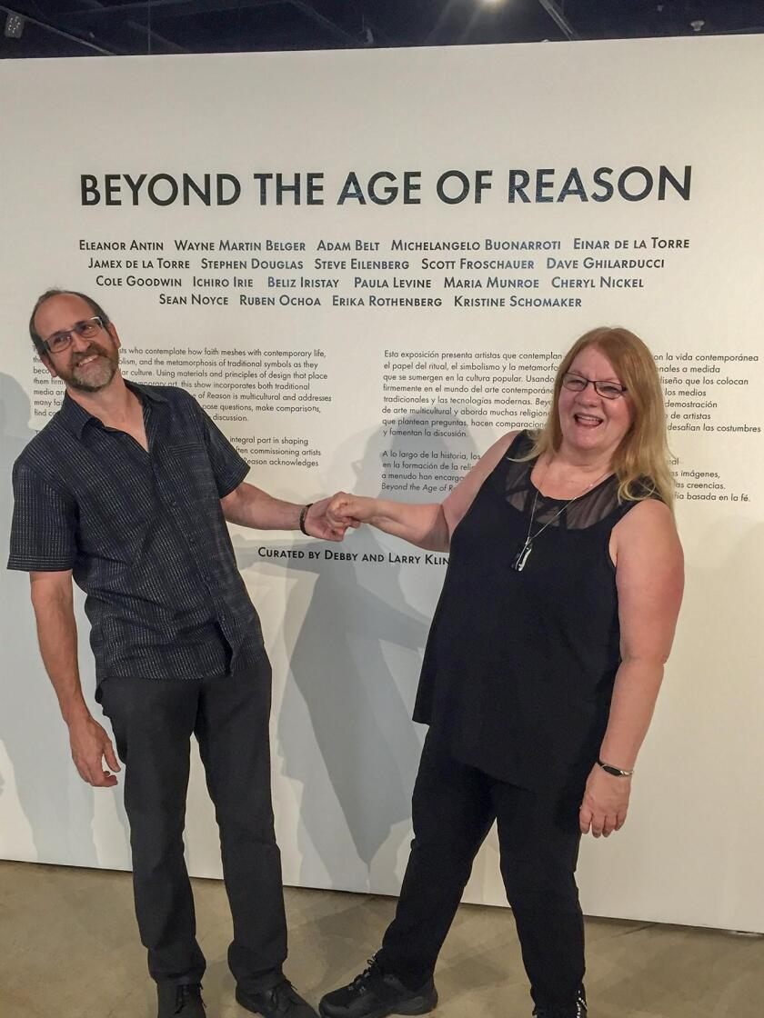 Larry and Debby Kline pose at the entry to the multi-faith-based exhibit they curated at San Diego Art Institute in Balboa Park, during the opening reception.