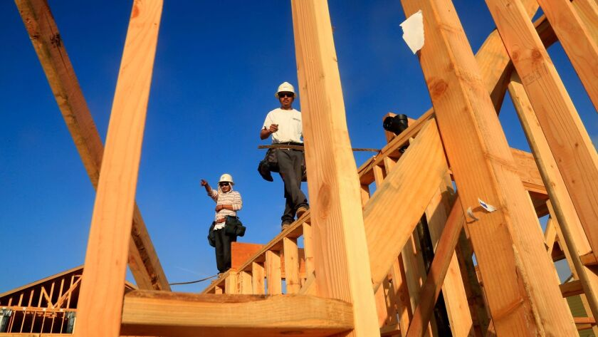 IRVINE,CA., MARCH 7, 2014: Framers walk along the top of the newly constructed walls of a home in t